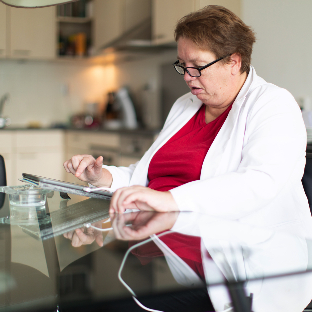 Angenita zit thuis aan de keukentafel en lest op haar tablet