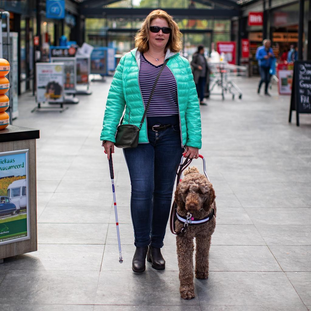 Susan is blind. Ze wandelt met haar geleidehond Ruby door een winkelcentrum