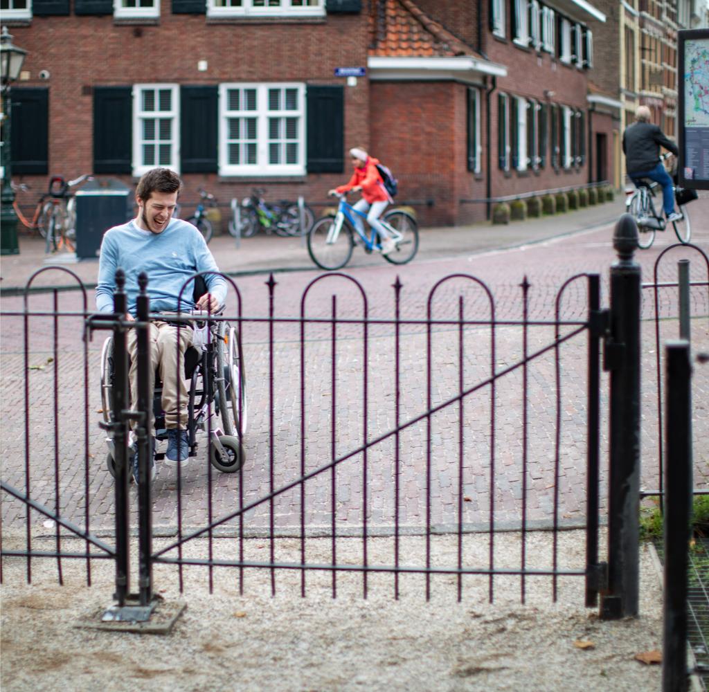 Timo rijdt in zijn rolstoel naar de ingang van een park. Er staat een hek waar hij niet doorheen kan.